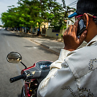 Jan 3, 2013 - A tuk tuk driver uses his mobile phone in the Cambodian capital city of Phnom Penh. <br /> <br /> Story Summary: Amidst the feverish pace of Phnom Penh&rsquo; city streets, a workhorse of transportation for people and goods emerges: Bicycles, motorcycles, scooters, Mopeds, motodups and Tuk Tuks roam in place of cars and trucks. Almost 90 percent of the vehicles roaming the Cambodian capital of almost 2.3 million people choose these for getting about. Congestion and environment both benefit from the small size and small engines. Business is booming in the movement of goods and and another one million annual tourists in Cambodia&rsquo;s moto culture.