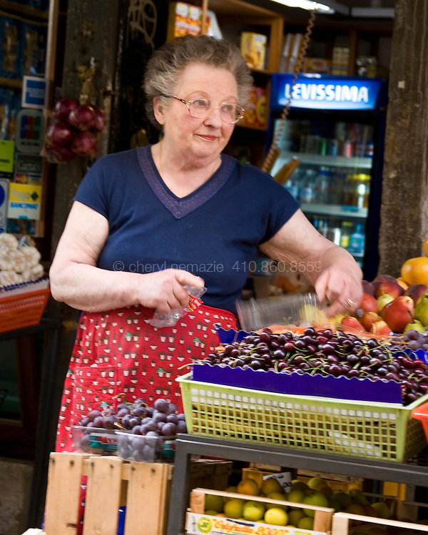 A woman prepares her produce for the day's shoppers.