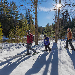 A couple and their daughter snowshoe next to the Hudson River near its source in New York's Adirondack Mountains. Upper Works Trail, Tahawus Tract, Newcomb, New York.