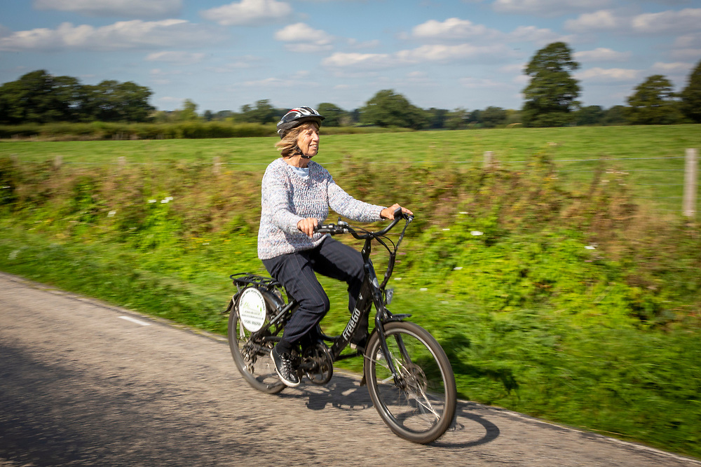 A mature woman happily cycles an electric bike along a country road by Hush Heath Winery, Staplehurst, Kent, England, UK. (photo by Andrew Aitchison / In pictures via Getty Images)