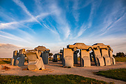 """Carhenge sunrise. Carhenge replicates England's Stonehenge using vintage American automobiles, near Alliance, Nebraska, in the High Plains region, USA. After studying Stonehenge in England, years later, Jim Reinders recreated the physical size and placement of Stonehenge's standing stones in summer 1987, helped by 35 family members. Reinders said, """"It took a lot of blood, sweat, and beers."""" Carhenge was built as a memorial to Reinders' father. 39 automobiles were arranged in the same proportions as Stonehenge with the circle measuring a slightly smaller 96 feet (29m) in diameter. Some autos are held upright in pits five feet deep, trunk end down, while other cars are placed to form the arches and welded in place. All are covered with gray spray paint. The heel stone is a 1962 Cadillac. Reinders donated Carhenge to the Friends of Carhenge, who gifted it to the Citizens of Alliance in 2013."""
