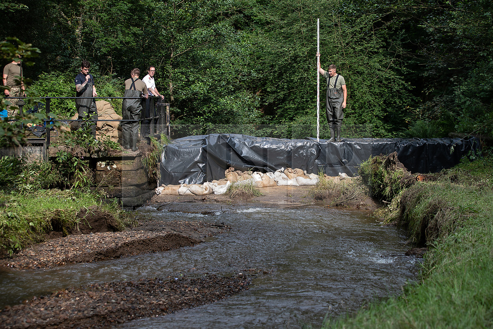 © Licensed to London News Pictures. 04/08/2019. Whaley Bridge, UK. A soldier from the Light Dragoons regiment , based out of Catterick , stands on a dam , which has been increased in height by 1 metre , and helps with a Canal and Rivers Trust survey monitoring fast-flowing water , as an upstream river is diverted via a sluice in to a bywater that runs parallel to the reservoir . More rain is forecast overnight (Sunday 4th/Monday 5th August) in the town of Whaley Bridge in Derbyshire after earlier heavy rain caused damage to the Toddbrook Reservoir , threatening homes and businesses with flooding. Photo credit: Joel Goodman/LNP