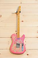 Pink paisley Fender guitar on wood grain wall