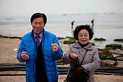 "Korean couple with mussels during low tide at Hoedong shore (Jindo Island). Jindo is the 3rd biggest island in South Korea located in the South-West end of the country and famous for the ""Mysterious Sea Route"" or ""Moses Miracle"" which is happening during full moon in spring."