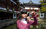 Young woman takes photograph on zigzag bridge at Yu Gardens Bazaar Market, Shanghai, China