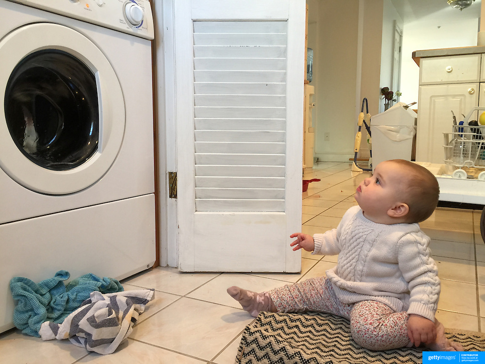 A nine month old baby girl watching the washing machine.  Photo Tim Clayton