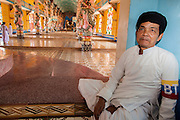 "29 MARCH 2012 - TAY NINH, VIETNAM:   A Cao Dai adherent watchs the main entrance of the prayer hall at the Cao Dai Holy See in Tay Ninh, Vietnam. Cao Dai (also Caodaiism) is a syncretistic, monotheistic religion, officially established in the city of Tây Ninh, southern Vietnam in 1926. Cao means ""high"" and ""Dai"" means ""dais"" (as in a platform or altar raised above the surrounding level to give prominence to the person on it). Estimates of Cao Dai adherents in Vietnam vary, but most sources give two to three million, but there may be up to six million. An additional 30,000 Vietnamese exiles, in the United States, Europe, and Australia are Cao Dai followers. During the Vietnam's wars from 1945-1975, members of Cao Dai were active in political and military struggles, both against French colonial forces and Prime Minister Ngo Dinh Diem of South Vietnam. Their opposition to the communist forces until 1975 was a factor in their repression after the fall of Saigon in 1975, when the incoming communist government proscribed the practice of Cao Dai. In 1997, the Cao Dai was granted legal recognition. Cao Dai's pantheon of saints includes such diverse figures as the Buddha, Confucius, Jesus Christ, Muhammad, Pericles, Julius Caesar, Joan of Arc, Victor Hugo, and the Chinese revolutionary leader Sun Yat-sen. These are honored at Cao Dai temples, along with ancestors.   PHOTO BY JACK KURTZ"