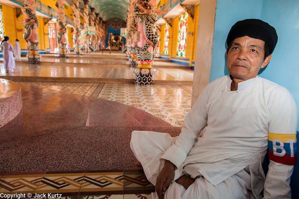 """29 MARCH 2012 - TAY NINH, VIETNAM:   A Cao Dai adherent watchs the main entrance of the prayer hall at the Cao Dai Holy See in Tay Ninh, Vietnam. Cao Dai (also Caodaiism) is a syncretistic, monotheistic religion, officially established in the city of Tây Ninh, southern Vietnam in 1926. Cao means """"high"""" and """"Dai"""" means """"dais"""" (as in a platform or altar raised above the surrounding level to give prominence to the person on it). Estimates of Cao Dai adherents in Vietnam vary, but most sources give two to three million, but there may be up to six million. An additional 30,000 Vietnamese exiles, in the United States, Europe, and Australia are Cao Dai followers. During the Vietnam's wars from 1945-1975, members of Cao Dai were active in political and military struggles, both against French colonial forces and Prime Minister Ngo Dinh Diem of South Vietnam. Their opposition to the communist forces until 1975 was a factor in their repression after the fall of Saigon in 1975, when the incoming communist government proscribed the practice of Cao Dai. In 1997, the Cao Dai was granted legal recognition. Cao Dai's pantheon of saints includes such diverse figures as the Buddha, Confucius, Jesus Christ, Muhammad, Pericles, Julius Caesar, Joan of Arc, Victor Hugo, and the Chinese revolutionary leader Sun Yat-sen. These are honored at Cao Dai temples, along with ancestors.   PHOTO BY JACK KURTZ"""