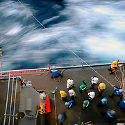 Deck department Sailors aboard the amphibious dock landing ship USS Fort McHenry (LSD 43) bring across a fuel line while conducting a refueling at sea with the amphibious assault ship USS Bataan (LHD 5).