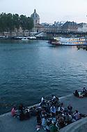 France. Paris.  1st district. people gathering for picnic at dusk on  the quay du Louvre, by the seine river  / les gens se retrouvent pour un pique nique sur  le quai du Louvre au bord de la seine