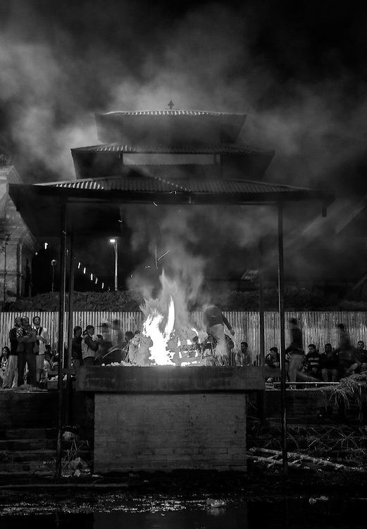 A funeral pyre burns on a cremation ghat along the sacred Bagmati River in Kathmandu, Nepal