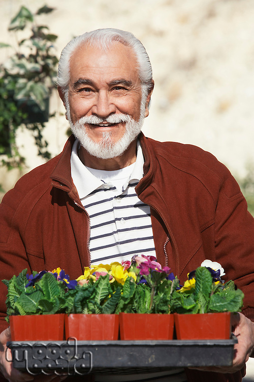 Elderly man holding tray with potted flowers