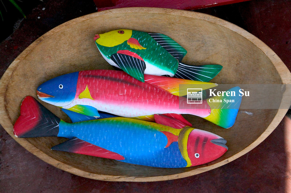 Colorfully painted wood fish in a wood bowl, Ecuador