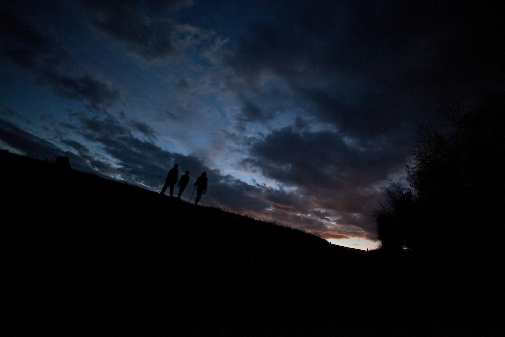 Silhouettes on a mountain top after sunset.