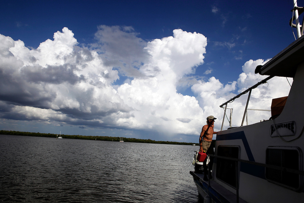 """Scot Janikula, 50, collects a gas can and heads to turn off his generator before heading into town. Janikula, has been living on a boat in Estero Bay for 13 years. Janikula says part of the attraction of living on a boat is that he doesn't have almost any bills to pay. """"You can't do anything on land without it costing money,"""" Janikula said."""