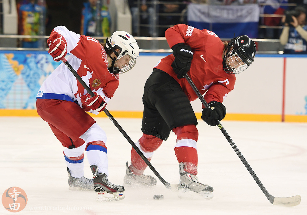 Feb 15, 2014; Sochi, RUSSIA; Switzerland defenseman Julia Marty (6) and Russia forward Alexandr Vafina (9) battle for the puck in a women's quarterfinals ice hockey game during the Sochi 2014 Olympic Winter Games at Shayba Arena.