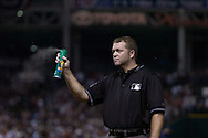 Umpire Ron Kulpa fires bug spray into the air during a bug raid in Game 2 of the 2007 ALDS at Jacobs Field in Cleveland.