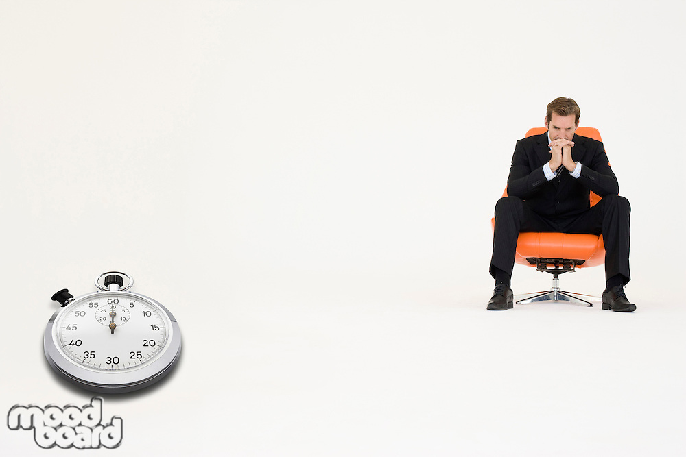 Anxious businessman sitting on chair with stopwatch showing time representing loss of time