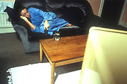 An teenage girl sleeping on the sofa with a blue dressing gown and glass of water standing on the table next to her, student accommodation, UK 2000's<br />