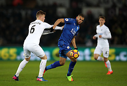 Swansea City's Alfie Mawson (left) and Leicester City's Islam Slimani battle for the ball during the Premier League match at the Liberty Stadium, Swansea.