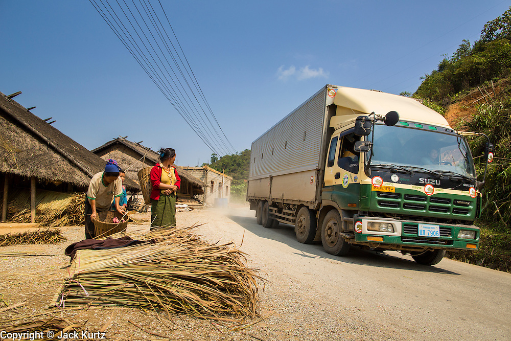10 MARCH 2013 - ALONG HIGHWAY 13, LAOS:  A truck hauling freight from China passes a Hmong village north of Vientiane. The paving of Highway 13 from Vientiane to near the Chinese border has changed the way of life in rural Laos. Villagers near Luang Prabang used to have to take unreliable boats that took three hours round trip to get from the homes to the tourist center of Luang Prabang, now they take a 40 minute round trip bus ride. North of Luang Prabang, paving the highway has been an opportunity for China to use Laos as a transshipping point. Chinese merchandise now goes through Laos to Thailand where it's put on Thai trains and taken to the deep water port east of Bangkok. The Chinese have also expanded their economic empire into Laos. Chinese hotels and businesses are common in northern Laos and in some cities, like Oudomxay, are now up to 40% percent. As the roads are paved, more people move away from their traditional homes in the mountains of Laos and crowd the side of the road living off tourists' and truck drivers.    PHOTO BY JACK KURTZ