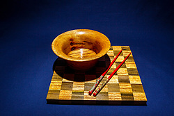 Hand turned wooden oak bowl on wooden checkerboard and dark blue background with decorated red colored chopsticks