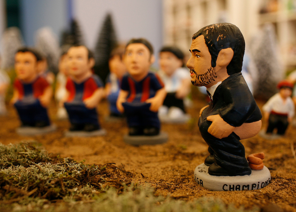 "Torroella de Mongri, Spain, 19 November 2009. .A company in Torroella de Montgrí (Girona, Spain) called ""caganer.com"" specialized in the production of ""caganers"" unveiled today  the new figures for Christmas as F.C. Barcelona coach, Josep Guardiola. .A ""Caganer"" is a small figure from Catalonia, usually made of fired clay,  and depicted as squating person in the act defecating. .""Caganer"" is Catalan for pooper. It fomrs part of one of the typical figures of  the manger or ""Nativity"" scene together with Mary, .Joseph and the baby Jesus but hidden in a corner. It is a humorous figure, originally portraying a peasant wearing a .barretina (a red stocking hat), and seems to date from the 18th century when it  was believed that the figure's depositions  .would fertilize the earth to bring a properous year. With  the course of the time, the original  personage of this pooping figure .was  substituted with personalities from the political and sports world and other famous personalities."