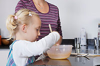 Girl and mother cooking together in kitchen