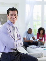 Portrait of business man in living room couple sitting in background