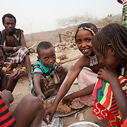 Kids are having a late breakfast after having finished their morning chores. The Afar diet is mainly milk with some rice or bread. The rice and flour is import to the region so its not every day they can eat that.  Action for Integrated Sustainable Development Association (AISDA) work in the AFAR region of Eastern Ethiopia, based in Delafagi. The Afars practise an old tradition of Female Genital Mutilation where the baby girls has her clitoris and labia cut away and her vagina sewn up. The day before her wedding day the girl is un-stiched ready for marriage. Its a brutal and barbaric tradition which AISDA is challenging with great effect, now more than a hundred girls in Dowe district have been saved from the knife and AISDA is now rolling out the scheme in Delafagi. Delafagi is where the oldest ever human remains have been found, the found is thought to be 4.5 mill years old.