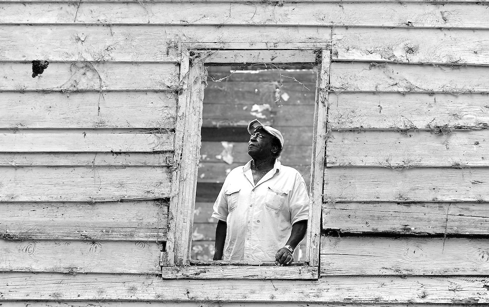 "Eighty-year-old Junior Meggett stands in the window of the 18th-century slave cabin his aunt and uncle lived in when he was a boy on Edisto Island, South Carolina. Historic records show the string of cabins, built by Charles Bailey in the 1840s or 1850s, housed some of the plantation's 75 slaves. Meggett said he lived in a neighboring cabin that was part of a ""slave street"" and his family worked on the plantation in the early 20th century. The cabin was recently dismantled and shipped to Smithsonian's new National Museum of African American History and Culture in Washington, D.C. (Stephen Morton for The New York Times)"