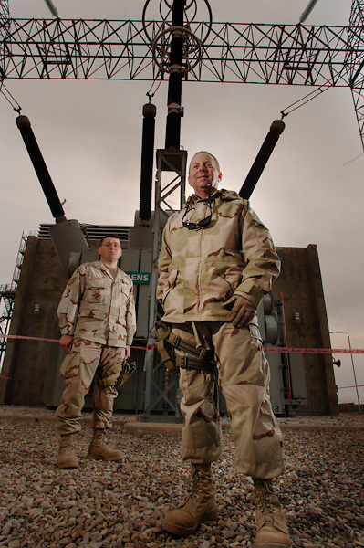 """Chief Master Sgt. Paul Kaplan (right) and Tech. Sgt. Billy D. Tramel (left)during a site survey of the transformer for a Siemens V94 generator that can produce 260 megawatts of electricity (equal to electricity for 200,000 homes). The transformer is connected directly to the 400,000-volt national power grid. Chief Master Sgt. Kaplan explains, """"oil and electricity are co-dependent"""" in Iraq's ability production and distribution.  Kaplan is a power and Oil Infrastructure Team (POInT) member in charge of electricity. In his region he aids the forward movement of the national power grid, which includes four major power plants and the Northern Region Control Center. The power grid supports Baghdad and the entire nation. He is deployed to the 732 Expeditionary Civil Engineering Squadron, Detachment at Kirkuk Air Base, Iraq. The San Diego native is stationed with the 60th Civil Engineering Squadron, Travis Air Force Base. Tech. Sgt. Billy D. Tramel supports the hardening valves, manifolds, and infrastructure in the oilfields of Kirkuk, Iraq. For the three-person power and oil infrastructure team (POInT) he constantly manages $23 million dollars worth of projects that support the flow of oil. The oil is critical to the rebuilding and independence or Iraq. The oil and natural gas from his region of responsibility east of the Tigris River and north of Balad fuels the Kirkuk power plant. Tech. Sgt. Tramel stationed with the 75th Civil Engineering Squadron, Hill Air Force Base, Utah, brings to the fight, degrees in Environmental Engineering, Business Administration, a certificate in Professional Engineering, and licenses in Master Plumbing, Waste Water Treatment and Water Treatment. His coordination have resulted in augmenting Iraqi pipeline security in this high threat region; building of a security training academy military; emergency vehicles; to playgrounds for the community, to name a few.  His greatest tool is tact in communication and cultural awareness. According to Majo"""