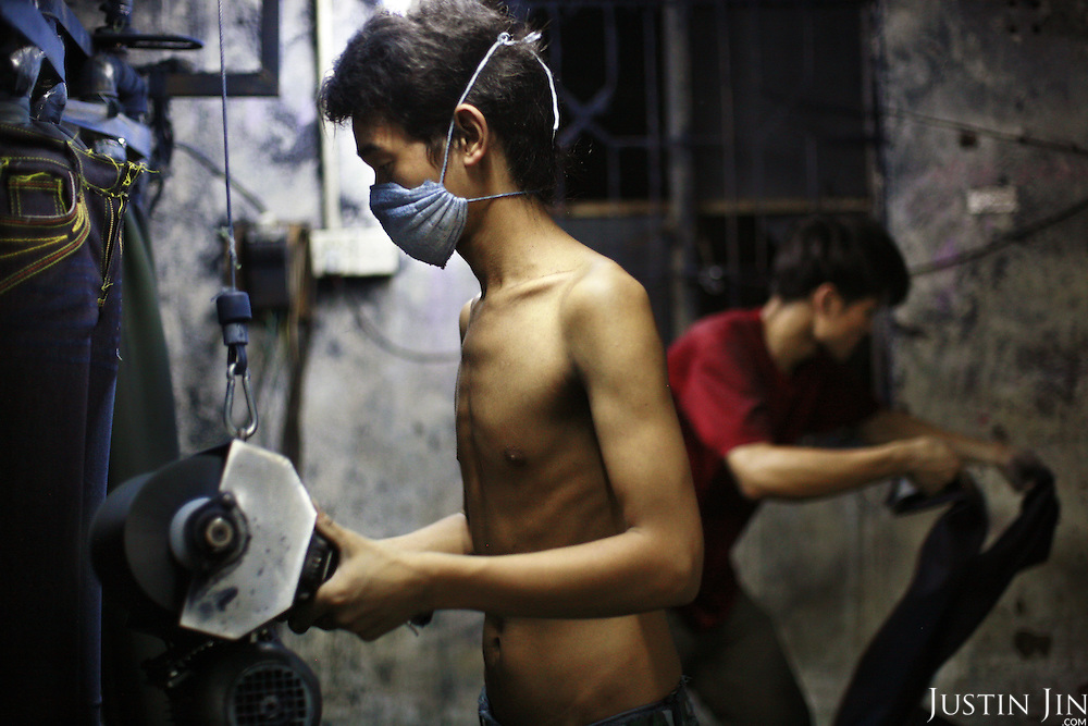 """Workers scrub jeans using a sanding machine in Mr Huang's factory in Zhongshan city, China..This picture is part of a photo and text story on blue jeans production in China by Justin Jin. .China, the """"factory of the world"""", is now also the major producer for blue jeans. To meet production demand, thousands of workers sweat through the night scrubbing, spraying and tearing trousers to create their rugged look. .At dawn, workers bundle the garment off to another factory for packaging and shipping around the world..The workers are among the 200 million migrant labourers criss-crossing China.looking for a better life, at the same time building their country into a.mighty industrial power."""