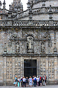 Tourists and tour guide at Quintana de Mortos gate of Cathedral of Santiago de Compostela, Galicia, Spain