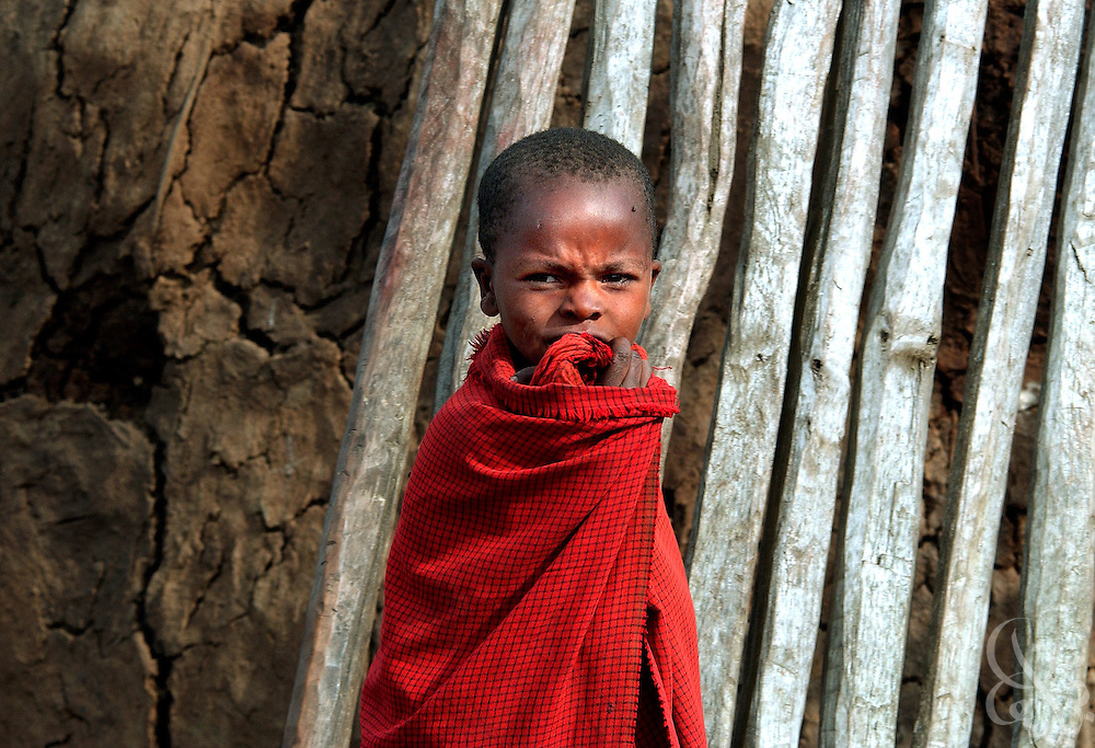 A Masai child stands outside his traditional family home home June 18, 2003 in a village in Tanzania.
