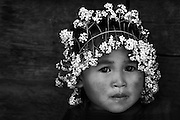 An Akha girl playing with a crown of flowers near Luang Namtha, Laos.