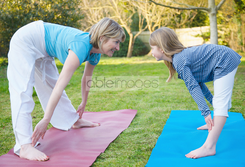 Mother and daughter practicing yoga in the garden