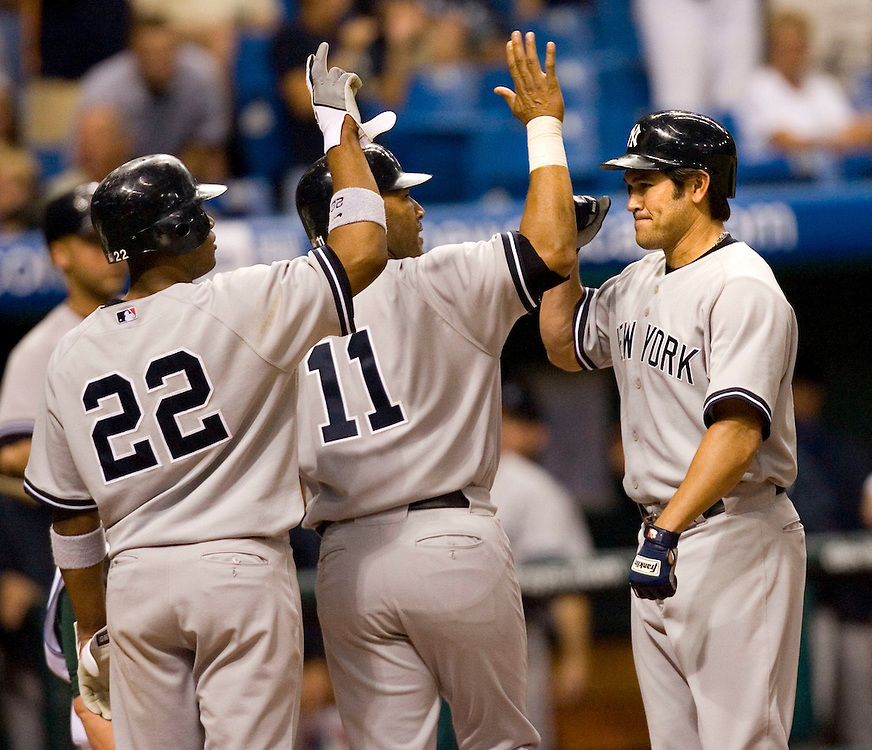 New York Yankees' Johnny Damon, right, is congratulated by teammates Gary Sheffield, center, and Robinson Cano, left, after Damon hit a grand slam driving in the two during the eighth inning of their American League baseball game against the Tampa Bay Devil Rays on Thursday, May 4, 2006 in St. Petersburg, Fla.(AP Photo/Scott Audette)