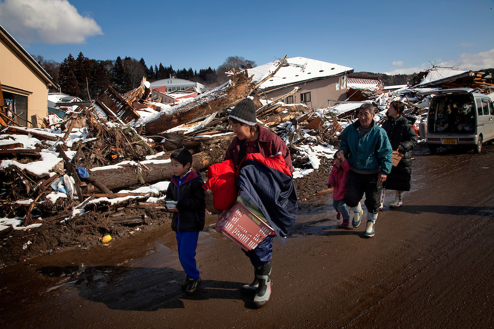 A family looks for their belongings amongst the debris of their destroyed house in the town of Taro where the earthquake and tsunami hit on 11 March 2011.