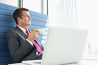 Mature businessman taking coffee break in office