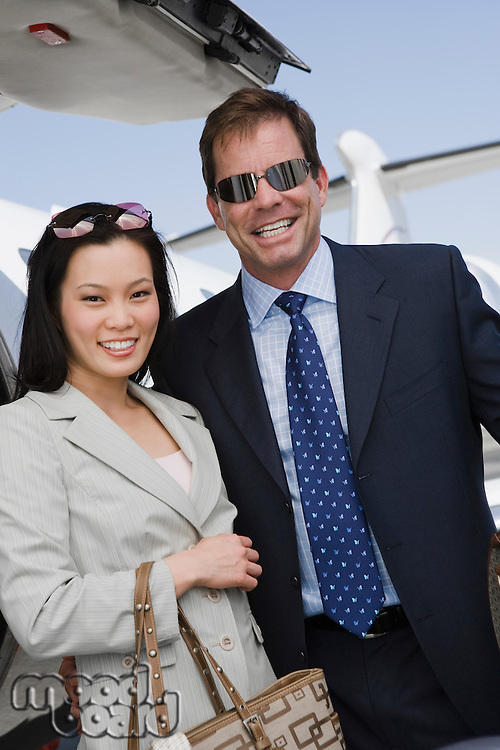 Mid-adult businesswoman and businessman standing in front of airplane.