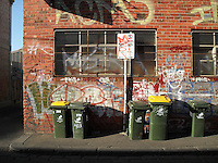Urban scene with wheelie bins and graffiti