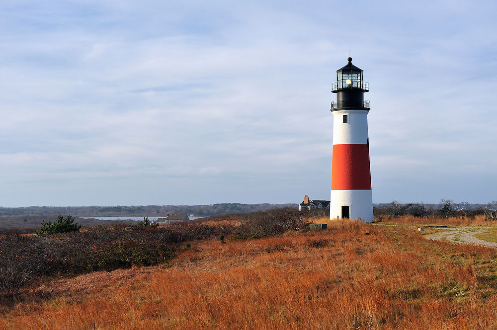 """The 70 foot tall red and white brick lighthouse was built in 1850. It was the first lighthouse in Massachusetts with a Fresnel lens, which was replaced in 1950 with a rotating aerobeacon. The light was automated in 1965 but Coast Guard personnel occupied the station until 1992. In 2007, the Sankaty Head Lighthouse was moved from the edge of an eroding bluff to its current location, 250 feet from the bluff's edge, near the fifth hole of the Sankaty Head Golf Course and overlooking the Nantucket moors. Sankaty, from the Indian """"sankoty,"""" means """"highland.""""."""