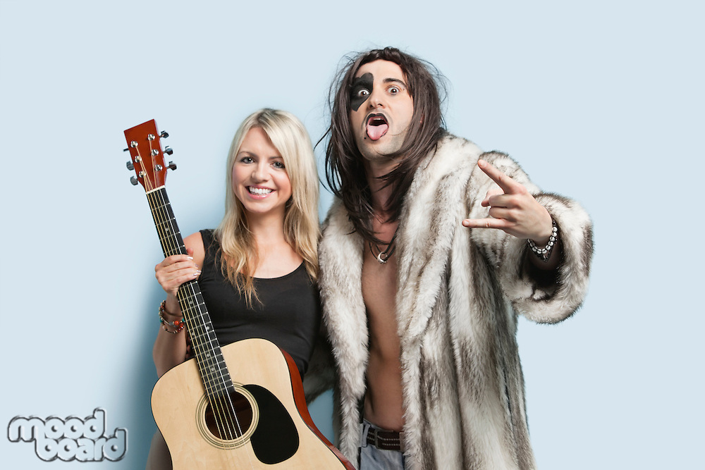 Portrait of happy young man gesturing with woman holding guitar against light blue background