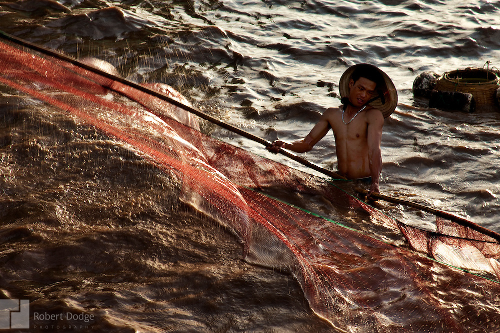 A fisherman battles the wind and tide to control his fishing net in the South China Sea at Bac Lieu Province. Robert Dodge, a Washington DC photographer and writer, has been working on his Vietnam 40 Years Later project since 2005. The project has taken him throughout Vietnam, including Hanoi, Ho Chi Minh City (Saigon), Nha Trang, Mue Nie, Phan Thiet, the Mekong, Sapa, Ninh Binh and the Perfume Pagoda. His images capture scenes and people from women in conical hats planting rice along the Red River in the north to men and women working in the floating markets on the Mekong River and its tributaries. Robert's project also captures the traditions of ancient Asia in the rural markets, Buddhist Monasteries and the celebrations around Tet, the Lunar New Year. Also to be found are images of the emerging modern Vietnam, such as young people eating and drinking and embracing the fashions and music of the West. His book. Vietnam 40 Years Later, was published March 2014 by Damiani Editore of Italy.