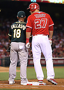 ANAHEIM, CA - APRIL 16:  Mike Trout #27 of the Los Angeles Angels of Anaheim towers over Alberto Callaspo #18 of the Oakland Athletics while standing on first base during the game against the Oakland Athletics at Angel Stadium on Wednesday, April 16, 2014 in Anaheim, California. The Angels won the game 5-4 in 12 innings. (Photo by Paul Spinelli/MLB Photos via Getty Images) *** Local Caption *** Mike Trout;Alberto Callaspo