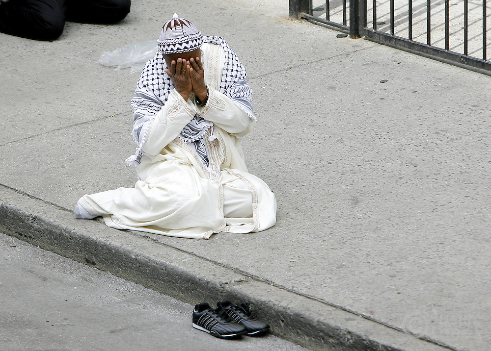 A man covers his face while sitting on the sidewalk during funeral services at the Islamic Cultural Center for the ten people killed in a recent house fire in the Bronx, New York on Monday 12 March 2007. Of the ten people killed in the fire, 9 were children, and all were immigrants from Mali.