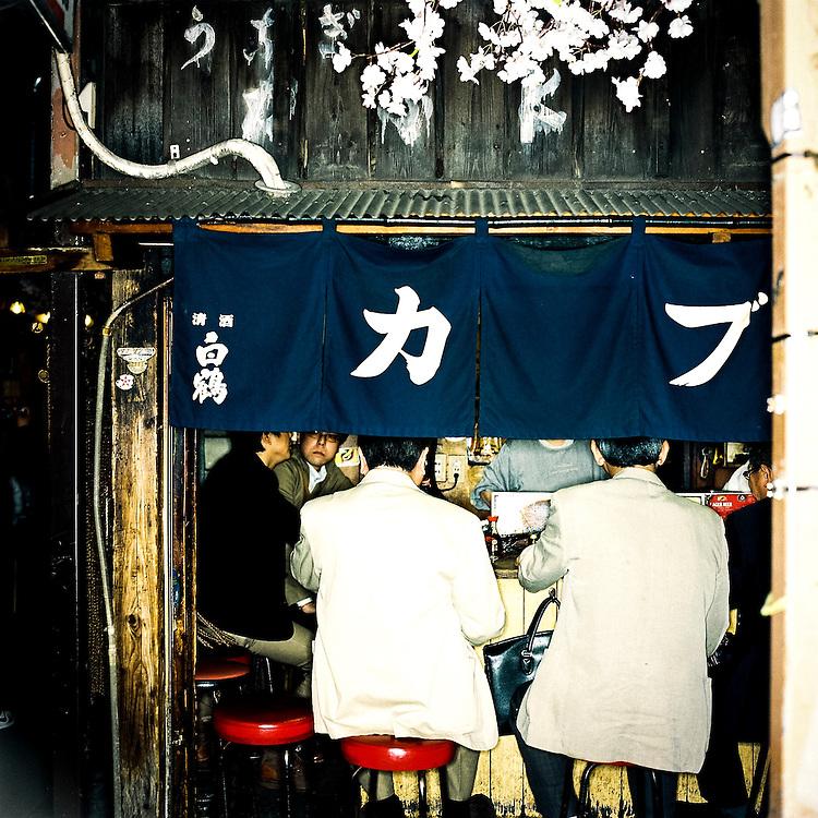 TOKYO, JAPAN - 2013 : Salarymen drinking in a small bar in Shinjuku Omoide Yokocho street an old remaining street in Shinjuku, Tokyo, Japan.<br /> <br /> Photo: Richard Atrero de Guzman