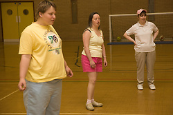 Group of woman day service user with learning disability fielding during an indoor cricket game in the gym