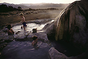 Route 395: Eastern Sierra Nevada Mountains of California. Bridgeport, Hot Spring. Jack and Evan Menzel and their friend Luke Sawyer enjoy the hot water with Luke's dad, Chris, who is drinking a beer. MODEL RELEASED.